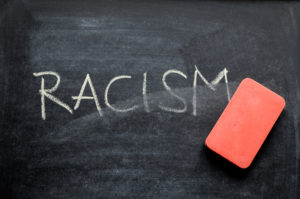 an eraser erasing the word racism on a chalkboard