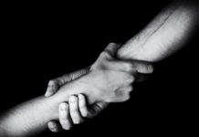 two people clasp arms