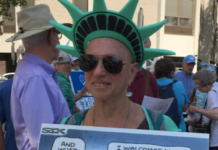 Phyllis Ocean Berman dressed as a statue of liberty holding a sign