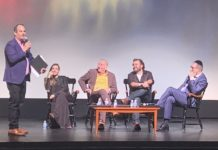 Eli Beer standing with Shtisel cast members and moderator sitting