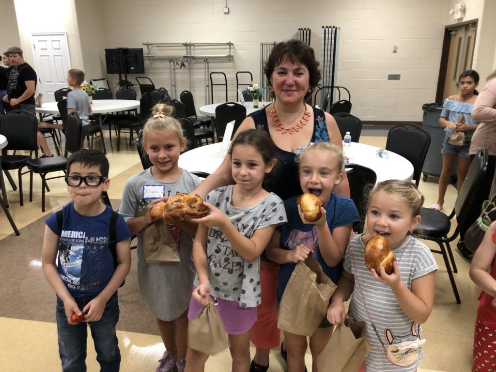 Victoria Faykin with children holding challah