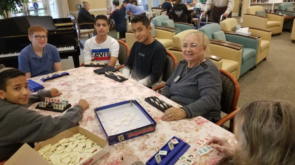 Abrams students play Rummikub with residents at Abrams Residence