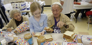Two elderly Jews and a young girl make peanut butter sandwhiches