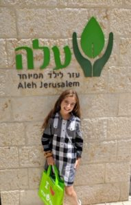 "Sedona Cohen in front of a sign that says ""AlLEH"" in Hebrew"