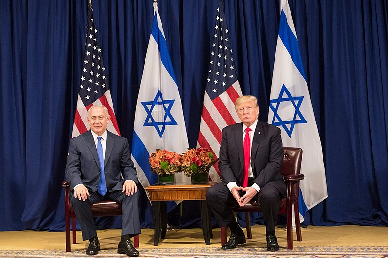 Benjamin Netanyahu and Donald Trump sitting in front of Israeli and American flags