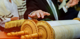 a hand hovers over a Torah scroll