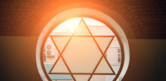 light shines though a window with a Jewish star