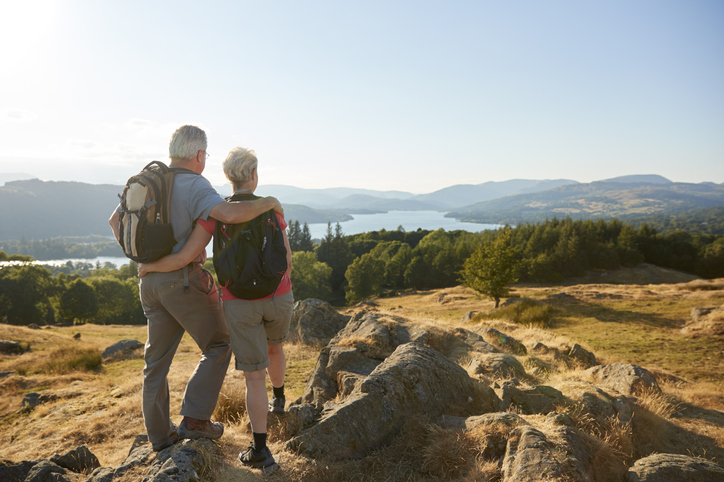 a retired couple gaze out on a hiking trail