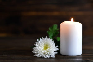 memorial candle next to a white flower