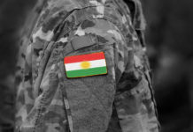 a soldier's uniform with a Kurdish flag