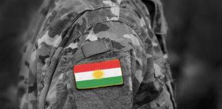 a soldier's uniform with a Kurdish flag