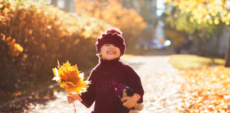little girl in red sweater holding fall leaves