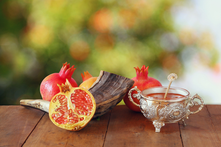 a shofar surrounded by pomegranates and a pot of honey