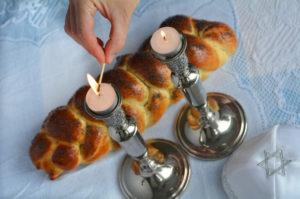 a woman lights shabbat candles next to a challah