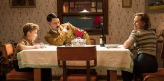 Roman Griffin Davis as Jojo has dinner with Taika Waititi as imaginary Hitler and Scarlett Johansson as his mother