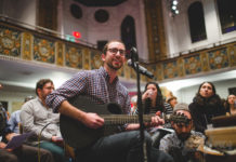 Rabbi Josh Warshawsky plays guitar and sings into a microphone at a synagogue