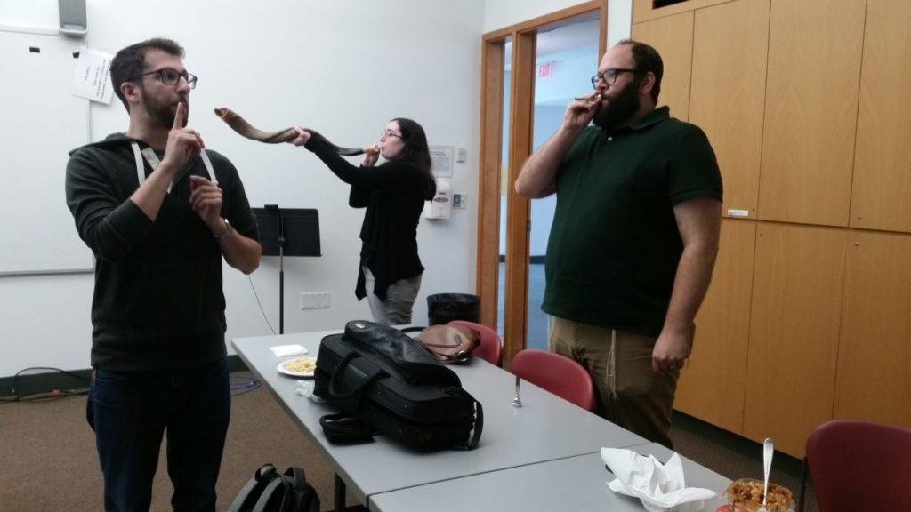 Matt Goldberg teaches other students how to blow the shofar