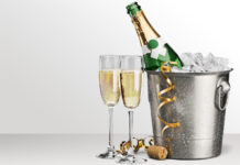 bottle of champagne in a bucket of ice with two glasses of champagne