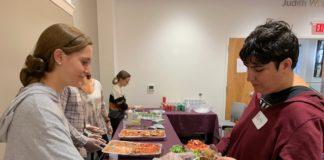 Talia Erlbaum serves food to Beth Barsky