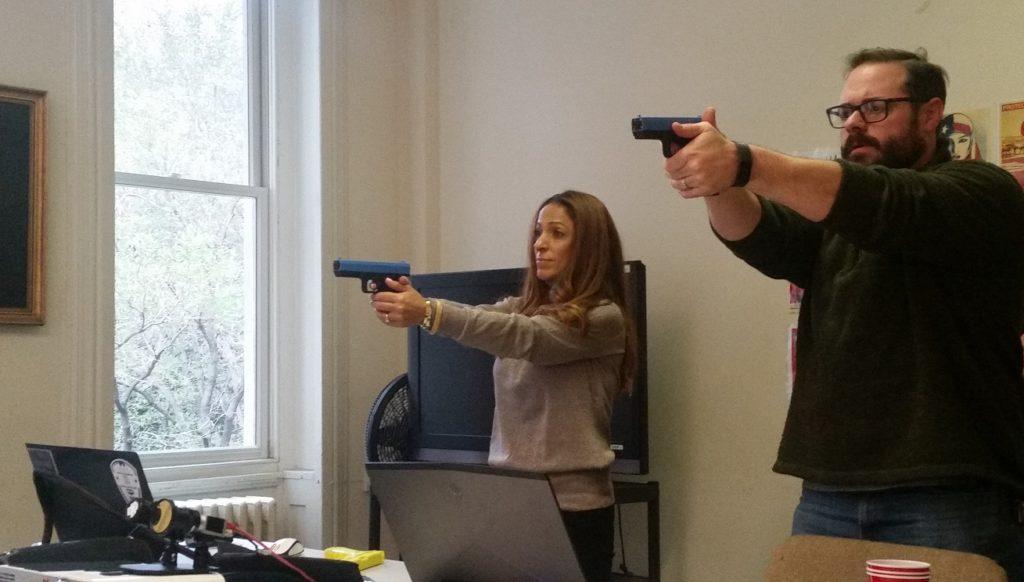 Dovrat Hadad and Richard Schmidt practice shooting in a Shot Tec firearm simulation