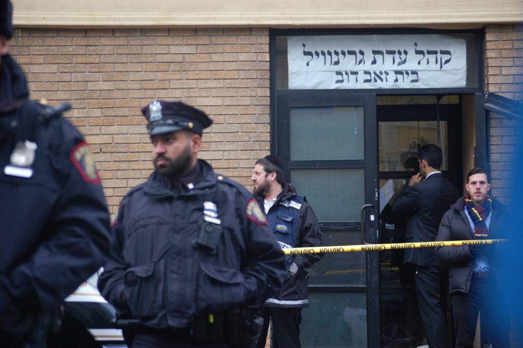 a group of people stand in front of K'hal Adas Greenville synagogue in Jersey City