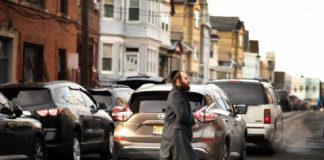 A Hasidic man crosses the street near the JC Kosher Supermarket