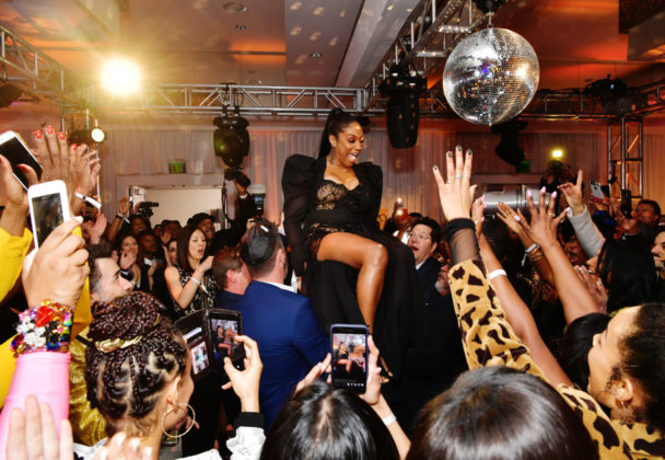 Tiffany Haddish is lifted in a chair