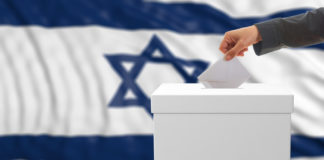 someone voting next to an Israeli flag