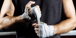 a man wraps strips of cloth on his hands in preparation for a wrestling match