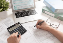 a person doing taxes with a laptop and calculator