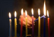 someone lights a Chanukah menorah