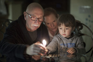 young child lights Chanukah candles with grandparents