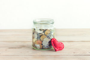 glass jar filled with coins next to a cloth heart