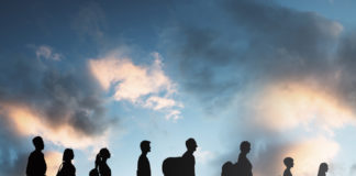 silhouettes of immigrants against a sky background