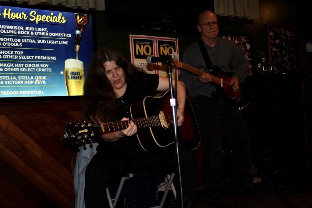 Nanette Arndts and Mark Furman play guitars