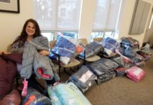 Tammy Spanier displays some of the new winter coats collected to donate to residents of Atlantic and Cape May counties.
