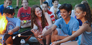 kids roast marshmallows at camp
