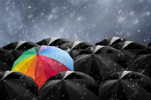 a colorful umbrella in a sea of black umbrellas