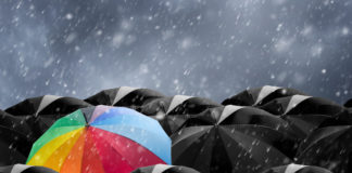 a colorful umbrella in a sea of black umbrellas
