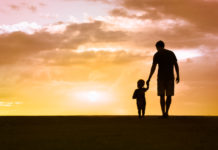 the silhouette of a father and son holding hands against a sunset