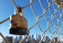 a lock on a fence in front of New York City