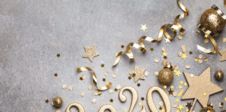 Holiday background with golden Christmas decorations and New year 2020 numbers and confetti stars top view.