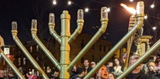 Rabbanit Dasi Fruchter lights a menorah at a Chanukah celebration in South Philadelphia