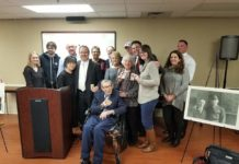 Max Gordon holds up his Congressional Gold Medal of Service
