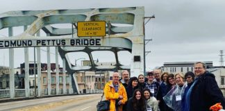 Mission partipants pose for a picture on Edmund Pettus Bridge, site of the Bloody Sunday attacks, in Selma, Alabama.