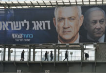 Blue and White political party election billboard with an image of Benny Gantz, party leader, in front of Benjamin Netanyahu, Israeli PM and Likud Party leader, seen in Ramat Gan. Israelis head to the polls for the third election in less than a year on March 2nd. On Tuesday, February 25, 2020, in Ramat Gan, Tel Aviv District, Israel.