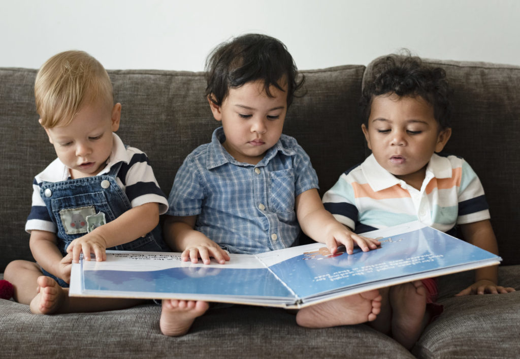 Three little boys reading a book on a sofa ***These are our own generic designs. They do not infringe on any copyrighted designs.