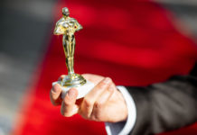Hand holding Oscar award.