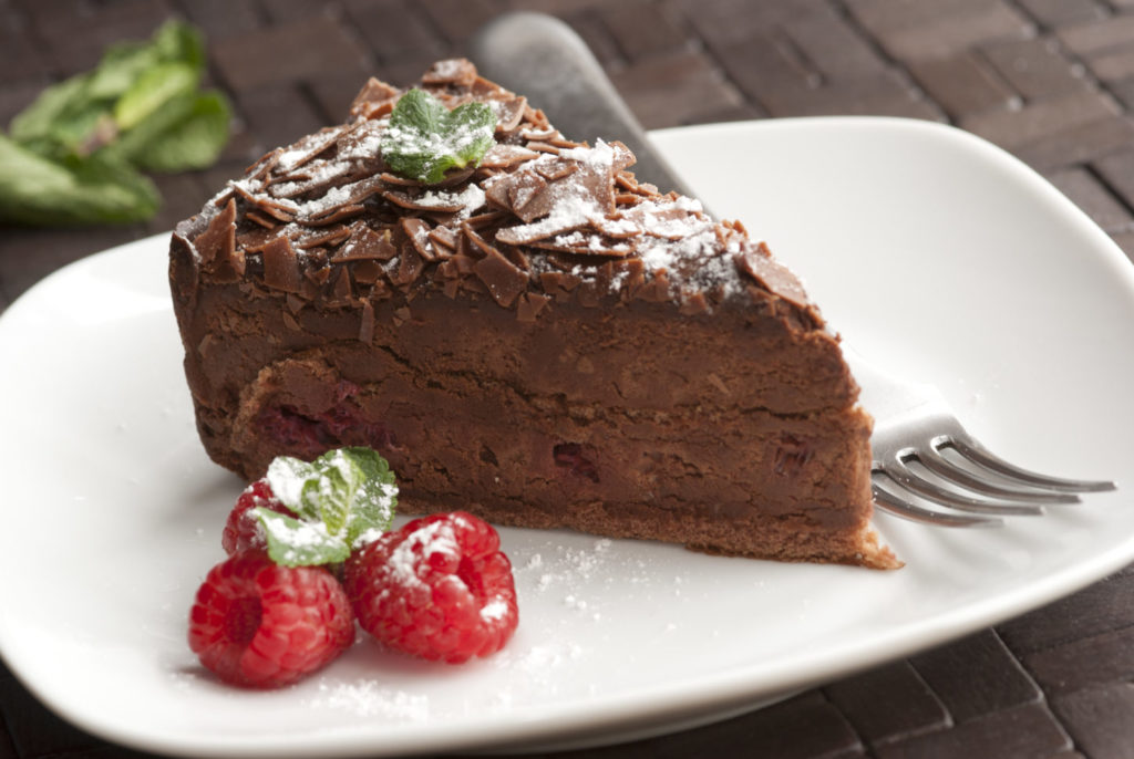 A piece of chocolate and raspberry torte on a plate.