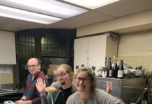 people posing for a photo in a kitchen